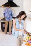 Woman chopping vegetables and man cooking on stove. Woman chopping vegetables and men cooking on stove in kitchen at home Stock Photos