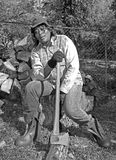Woman chopping wood. An African American woman taking a break from chopping wood royalty free stock photography