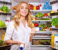 Woman chosen yogurt in opened refrigerator Royalty Free Stock Photo