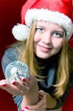 Woman and christmas ball on red. Portrait of beautiful blond young woman wearing santa claus and christmas ball on red Royalty Free Stock Image