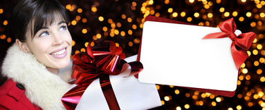 Woman with christmas box and gift card in golden lights Stock Photo