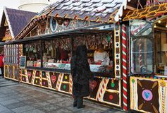 Woman at Christmas candy house and visitors in Vilnius Lithuania. Vilnius, Lithuania - December 4, 2016: Woman at Christmas candy house on Xmas market on royalty free stock images