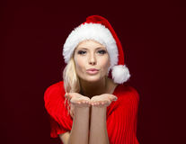 Woman in Christmas cap blows kiss Stock Images