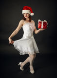 Woman in Christmas cap with a celebratory gift Royalty Free Stock Image