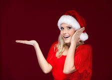 Woman in Christmas cap gestures palm up Royalty Free Stock Photography