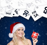 Woman in Christmas cap hands present. Season sales Stock Photos