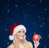Woman in Christmas cap hands present wrapped with red paper Stock Photo