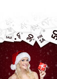 Woman in Christmas cap offer special price on gift Stock Photography