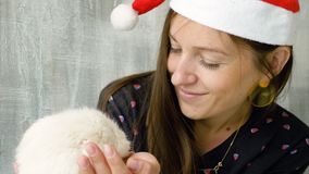 Woman in Christmas cap with white domestic rat. Portrait Of Young Caucasian Woman In Red Christmas Cap Hold White Rat stock footage