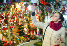 Woman at Christmas fair in evening. Portrait of excited smiling young woman choosing gifts and decorations at Christmas fair in evening Royalty Free Stock Photos