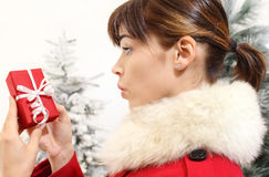 Woman with Christmas gift, amazed Stock Photo
