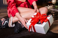 A woman with a Christmas gift, a box with a red ribbon sitting on the floor stock photos