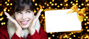 Woman with christmas gift card in golden lights. Background Royalty Free Stock Image
