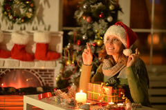 Woman with Christmas gift. Portrait of smiling woman with Christmas gift ar home  keeps fingers crossed Stock Photography