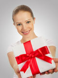 Woman with a Christmas gift with red ribbon in t. Beautiful young woman with a Christmas gift with red ribbon in their hands on a gray background Stock Photography