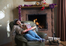 Woman with Christmas gifts by the fireplace. In the armchair Stock Image