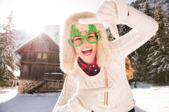 Woman in Christmas glasses framing with hands in the countryside Royalty Free Stock Photos