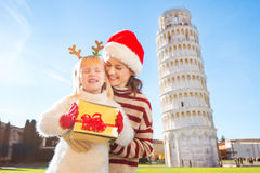 Woman in Christmas hat and baby girl holding gift box. Pisa Royalty Free Stock Images