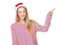 Woman with Christmas hat and finger point aside Stock Photo