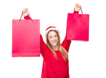 Woman with Christmas hat and hold up the paper bag Stock Photos