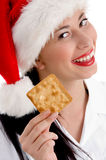 Woman with christmas hat and holding biscuit Stock Photography