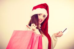 Woman in Christmas hat holds credit card and shopping bags. Royalty Free Stock Image
