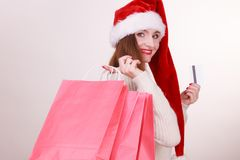 Woman in Christmas hat holds credit card and shopping bags. Royalty Free Stock Images