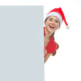 Woman in Christmas hat looking out from billboard Royalty Free Stock Images