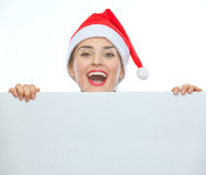 Woman in Christmas hat looking out from billboard Stock Photo