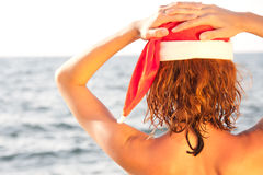 Woman in christmas hat looking at the sea Royalty Free Stock Images