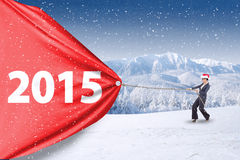 Woman with christmas hat and number 2015. Female entrepreneur wearing christmas hat and pulling number 2015 outdoors Stock Photo