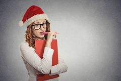 Woman with christmas hat is posing in studio thinking of gift ideas Royalty Free Stock Image