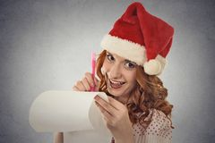 Woman with christmas hat is posing in studio writing gift ideas Royalty Free Stock Photo