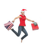 Woman in Christmas hat with shopping bags jumping Royalty Free Stock Images