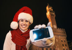 Woman in Christmas hat showing smartphone`s blank screen, Italy Royalty Free Stock Images