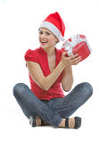 Woman in Christmas hat sitting on floor with gift Stock Images
