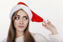 Woman in christmas hat thinking aboute somthing interesting Stock Photography