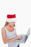 Woman with a Christmas hat using a laptop Stock Image