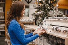 Woman at christmas market choosing decoration and white and silver balls for Christmas tree in New Year shop. Brunette stock images
