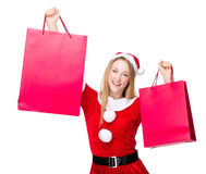 Woman with christmas party dress and hold up with shopping bag. Isolated over white background Royalty Free Stock Photo