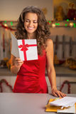 Woman with christmas postcard in kitchen Stock Photography