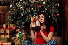 Woman with christmas present box on background decorated christmas tree. Brunette in a red shirt. Royalty Free Stock Images