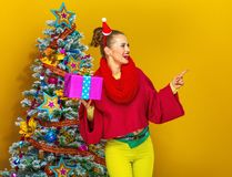 Woman with Christmas present box pointing at something Royalty Free Stock Images