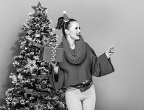 Woman with Christmas present box pointing at something Stock Photo