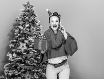 Woman with Christmas present box speaking on a smartphone. Festive season. happy stylish woman in colorful clothes near Christmas tree on yellow background with Royalty Free Stock Image