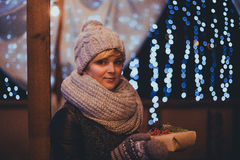 Woman with christmas present in hands near christmas lights Stock Images