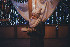 Woman with christmas present in hands near christmas lights Royalty Free Stock Photos