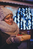 Woman with christmas present in hands near christmas lights Royalty Free Stock Image