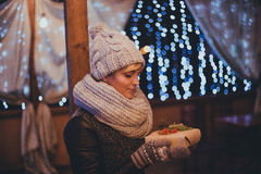 Woman with christmas present in hands near christmas lights Stock Photos