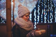 Woman with christmas present in hands near christmas lights Royalty Free Stock Photography